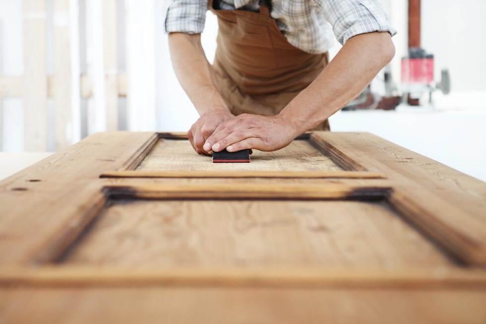 Tischler bearbeitet Holztür mit Schleifpapier